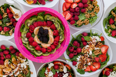 Bowls of assorted gourmet fresh salads with baby spinach leaves, seasonal fruit, feta cheese and walnuts viewed as a full frame background from above Banque d'images - 94656074