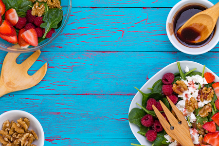 Side borders of fresh spinach salads with feta cheese, nuts and berries, shelled walnuts and vinaigrette sauce on a crackle paint blue wood background Banque d'images - 94656076