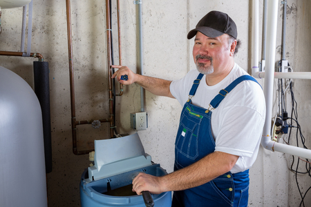 Friendly smiling workman in dungarees installing or working on a water softener in a utility room turning to smile at the camera 写真素材