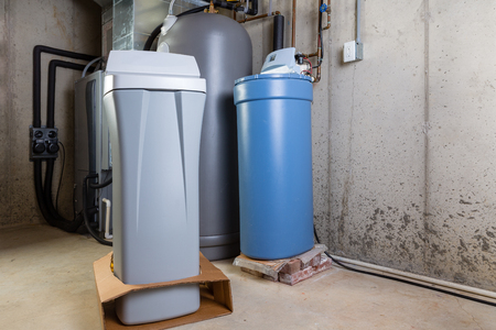 Old and new water softener tanks in a utility room waiting for replacement to remove minerals from hard water Stockfoto