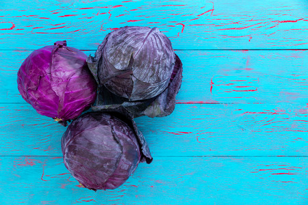 Three healthy fresh heads of red or purple cabbage, also known as red kraut, over a blue crackle paint wood background with copy space viewed from above