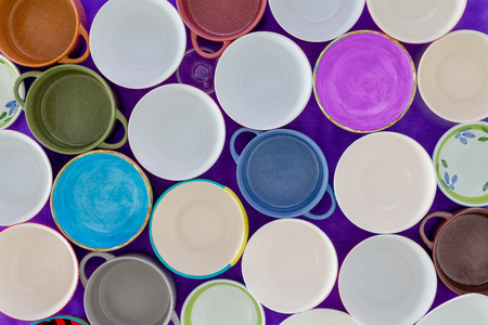 Overhead view of tightly packed assorted empty clean cups in a concept of hunger or thirst in a full frame background