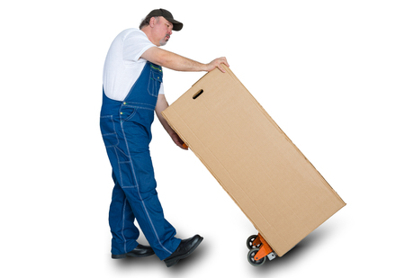 Deliverer transporting large cardboard box using trolley against white background Stock Photo