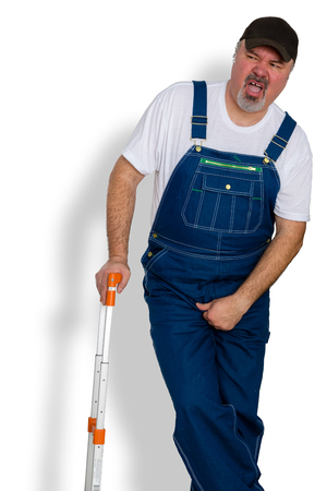 Worker in overalls clutching his groin in discomfort grimacing in pain as he needs desperately to use a bathroom facility to urinate over white