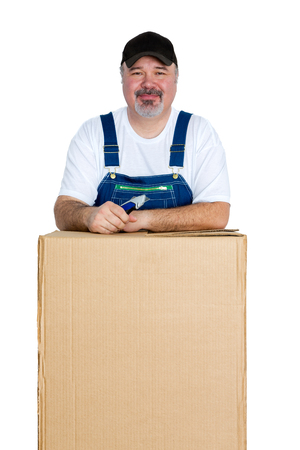 Portrait of cheerful man standing over large cardboard box against white background