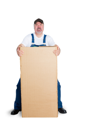 Delivery man standing behind large cardboard box against white background Foto de archivo