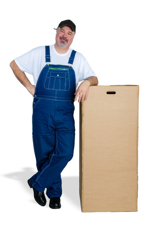 Cheerful delivery man leaning against large cardboard box
