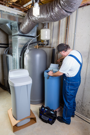 Experienced home installer fixing issues encountered on a new water softener tank that he is installing using his tools in a utility room in a basement Stok Fotoğraf