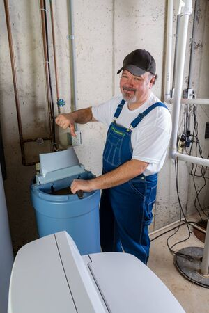 Hopeless home installer having trouble installing a new household water softener giving a thumbs down gesture with a rueful smile