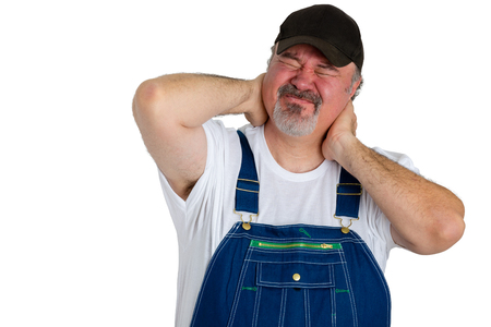 Workman in bib overalls with neck pains or a work related injury gripping the back of his head grimacing in pain isolated on white