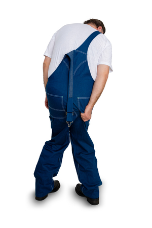 Male worker desperate to go to the toilet standing with his back to the camera and one strap of his dungarees undone clenching his knees together isolated on white Foto de archivo