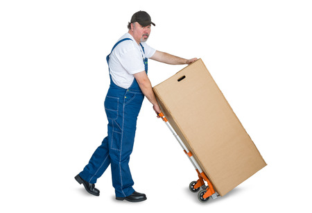 Male worker transporting large cardboard box with trolley against white background Stock Photo
