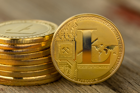 Pile of coins with Litecoin sign logo on wooden table with copy space in close-up. Cryptocurrency investment concept 写真素材