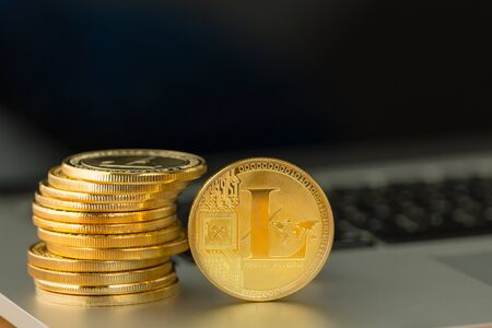 Single gold Litecoin coin alongside a stack in a concept of a digital cryptocurrency, exchange, finances, and investment on an open laptop computer with copy space