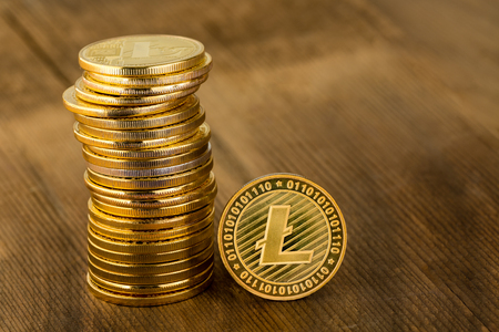 Single gold Litecoin coin balanced upright alongside a stack in a concept of a digital cryptocurrency, finances, and investment on wood with copy space Stock Photo