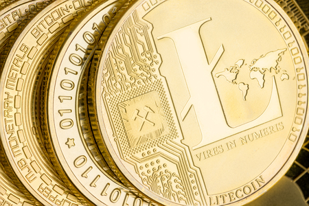 Detail of a gold Litecoin cryptocurrency coin showing the design and embossing on a stack of coins in a financial, investment, exchange and peer-to-peer payment concept
