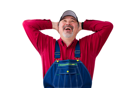Cheerful worker wearing dungarees standing against white background