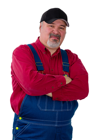 Farmer in dungarees standing sneering at the camera with folded arms and a supercilious expression isolated on white Stock Photo