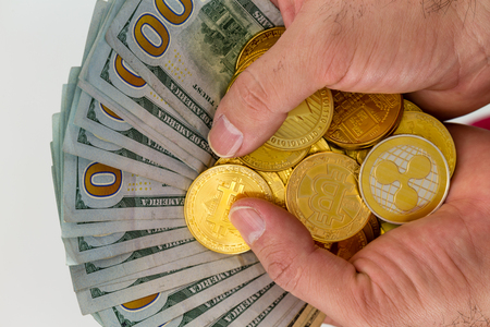 Hands holding bundle of dollars with golden coins