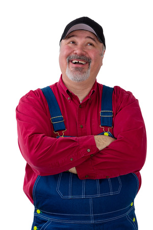 Pleased successful farmer in bib overalls or dungarees standing with folded arms looking up with a happy smile isolated on white