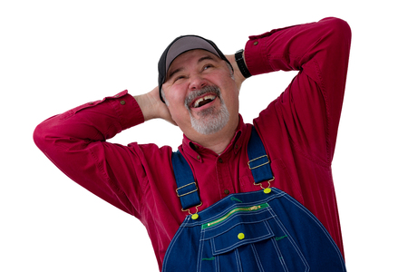 Joyful farmer or worker in bib overalls laughing in delight as he looks up with hands clasped behind his head on white