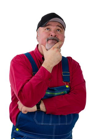 Confused slow-witted worker or farmer standing with his hand to his chin looking up with an expression of deep concentration isolated on white Stock Photo