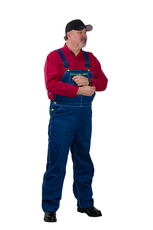 Full length portrait of a farmer or worker in denim dungarees standing looking thoughtfully to the side isolated on white