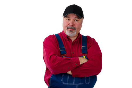 Portrait of man wearing dungarees standing with arms crossed against white background Stock Photo