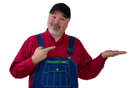 Middle-aged farmer or worker wearing a denim bi overall pointing to his empty hand over white copy space with a knowing expression of satisfaction