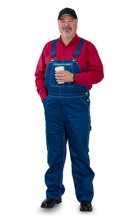 Relaxed confident farmer, gardener of laborer standing with his hand in his pocket holding coffee looking at the camera with a smile, full length on white