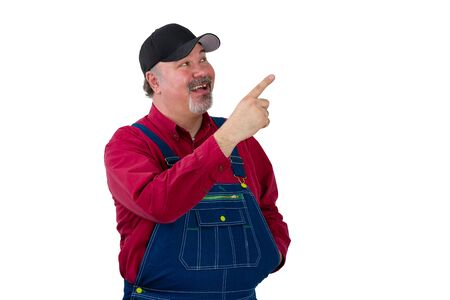 Pleased happy man in denim dungarees pointing up drawing your attention towards blank white copy space with a beaming smile Stock Photo