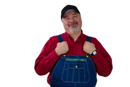Middle-class farmer, worker, laborer or gardener standing holding the straps on his dungarees looking at the camera with a proud pleased smile isolated on white