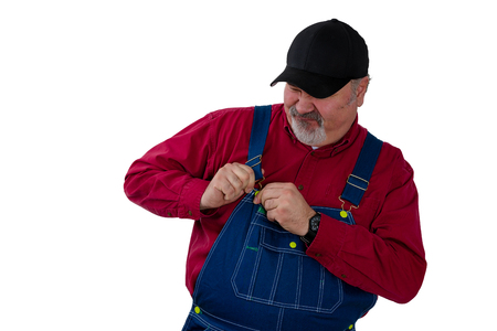 Farmer or worker fiddling with the fastener on his bib overalls as he attempts to dress or undress isolated on white Stock Photo