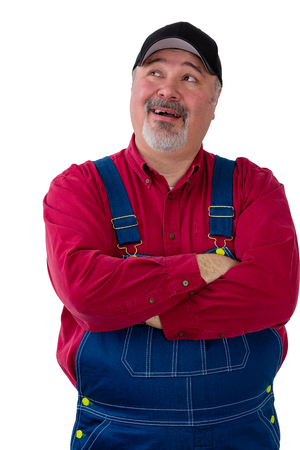 Farmer or worker in dungarees looking up to the side with his mouth open as though speaking isolated on white Stock Photo