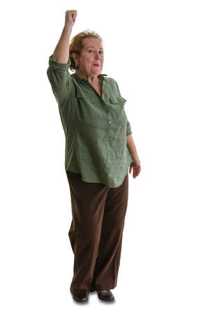 Portrait of enthusiastic senior woman raising hand while standing against white background Stock Photo