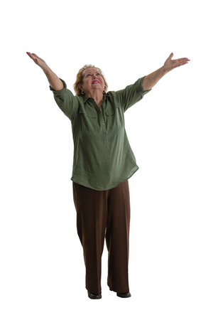 Smiling senior woman standing with welcoming gesture against white background Stock Photo