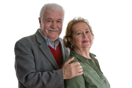 Studio portrait of cheerful senior couple standing against white background