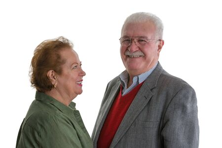 Portrait of cheerful senior woman looking at smiling elderly man against white background Stock Photo