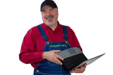 Laughing genial worker or farmer wearing denim dungarees standing holding an open laptop, upper body portrait isolated on white