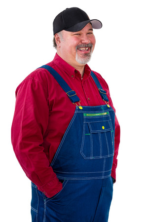 Smiling relaxed worker or farmer in overalls standing with his hands in pockets turned to the side with a look of amusement isolated on white