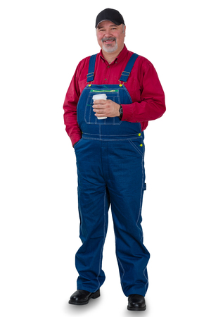 Full length portrait of a worker in denim dungarees, cap and red shirt standing smiling at the camera holding a cup of takeaway coffee isolated on white 写真素材