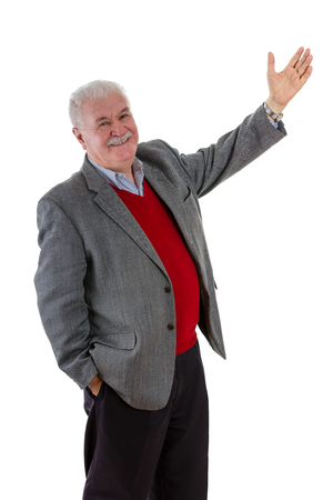 Smiling relaxed happy senior man with raised arm and other hand in his pocket turning to smile at the camera as he draws your attention to something isolated on white Stock Photo