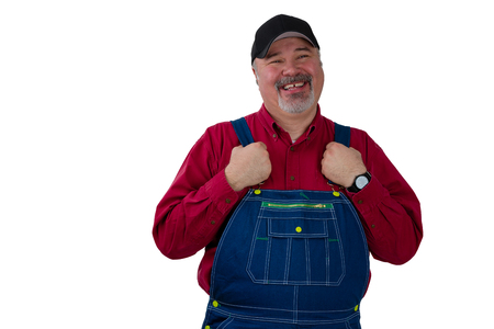 Middle-aged worker in dungarees with a proud smile holding the straps of his overalls as he grins at the camera isolated on white Stock Photo