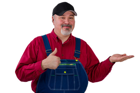 Farmer holding out his empty palm with copy space and giving a thumbs up of approval with a pleased smile over white Stock Photo