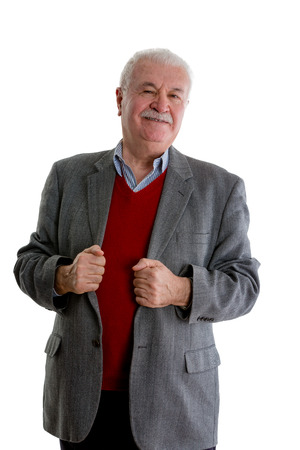 Suspicious senior man looking sceptically at the camera as he stands gripping the lapels of his jacket isolated on white