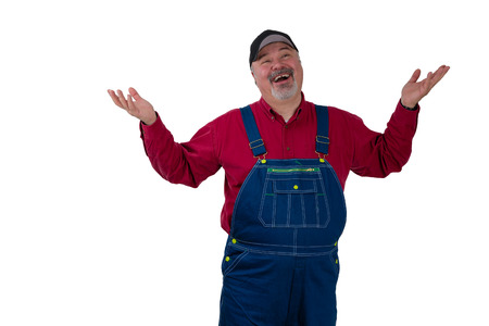 Laughing big-hearted magnanimous man in denim dungarees and cap standing holding open his arms with a beaming smile on white