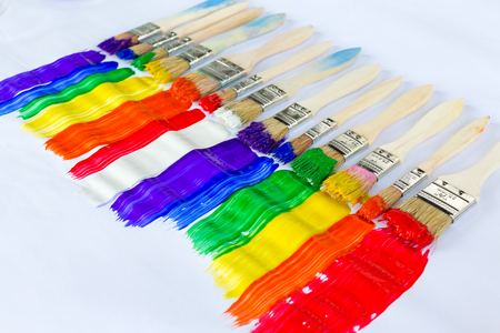Row of paint brushes with brightly colored paint in parallel stripes in the colors of the spectrum or rainbow in a diagonal line on white paper with copy space conceptual of art and creativity Stock Photo