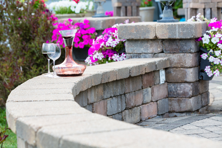 Decanter of red wine aerating on a curved brick patio wall with two wineglasses in front of colorful potted summer flowers with copy space