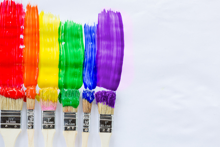 Colorful paint brushes against white paper with copy space