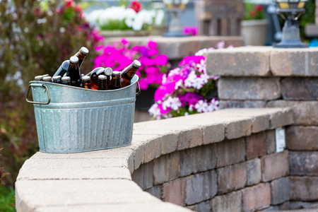 Galvanised metal tub filled with bottles of craft beer or larger chilling on a curved brick patio wall outdoors ready for a party or summer picnic Banco de Imagens